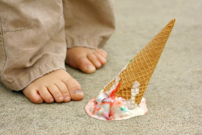 a dropped rainbow coloredFood Borne Illness ice cream cone lays upside down on the sidewalk at the feet of a young child